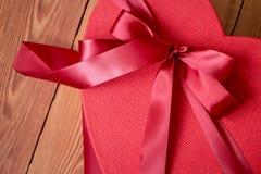 Gift of giftdoos met een rode boog van een lint in de vorm van een hart op een rustieke achtergrond voor Valentijnskaartendag royalty-vrije stock afbeelding