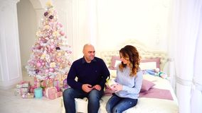 Gift of gifts from husband and wife, happy married couple in festive mood, sit on bed in bedroom with Christmas tree. Handsome man and husband hands gift box to stock footage