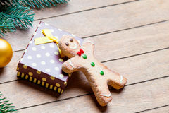Gift, gingerbread man and fir tree branch with bauble on the won Stock Photos