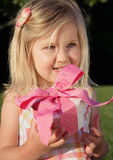 Gift Girl. Pretty little girl in sundress holding a pink birthday present outdoors in summer Stock Image