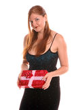 Gift Giver. Woman at a holiday party offers a christmas present Royalty Free Stock Image