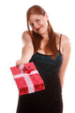Gift Giver. Woman at a holiday party offers a christmas present Royalty Free Stock Photos