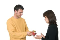 Gift giving. A handsome guy gives an asian girl a christmas present Stock Photography