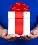 Gift giving. Hands giving a christmas gift royalty free stock photography