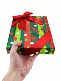 Gift Giving. Hand holding out a christmas present, isolated on white Stock Image