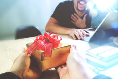 Gift Giving.business creative designer hand giving his colleague Stock Photos