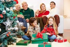 Gift giving at christmas eve. Chrildren making gift giving at christmas eve with family stock photos