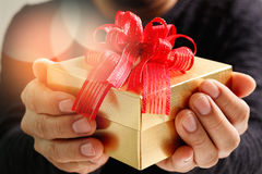 gift giving,man hand holding a gift box in a gesture of giving.blured background royalty free stock photos