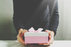 gift giving,man hand holding a gift box in a gesture of giving.blured background stock images