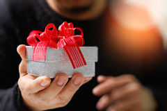 gift giving,man hand holding a gift box in a gesture of giving.b Royalty Free Stock Photos