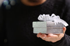 gift giving,man hand holding a gift box in a gesture of giving.b Royalty Free Stock Images