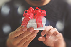 gift giving,man hand holding a gift box in a gesture of giving.blurred background,bokeh effect royalty free stock photo