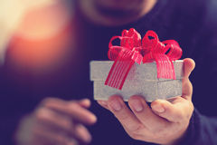 gift giving,man hand holding a gift box in a gesture of giving.b Royalty Free Stock Photography