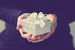 gift giving,man hand holding a gift box in a gesture of giving.blurred background,bokeh effect,vintage stock photography
