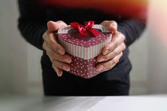 gift giving,man hand holding a gift box in a gesture of giving.b Stock Images