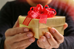 gift giving,man hand holding a gift box in a gesture of giving.b Stock Photos