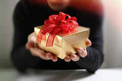 gift giving,man hand holding a gift box in a gesture of giving.b Stock Photography