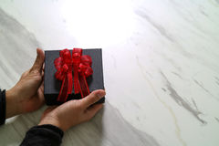 gift giving, man hand holding a gift box in a gesture of giving o royalty free stock photography