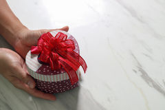 gift giving,man hand holding a heart shape gift box in a gesture Royalty Free Stock Image