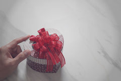 gift giving,man hand holding a heart shape gift box in a gesture Royalty Free Stock Photos