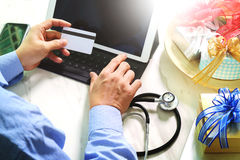 Gift giving,medical doctor Hand with credit card and hand with g Royalty Free Stock Image
