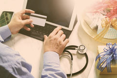 Gift giving,medical doctor Hand with credit card and hand with g Royalty Free Stock Photography