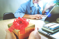 Gift Giving.Patient hand or Team giving a gift to a surprised Me. Dical Doctor in hospital office,filter film effect Royalty Free Stock Image