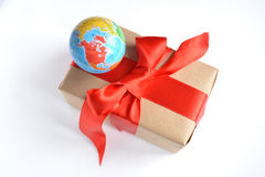 Gift with globe. Gift in a box with a big red bow and a toy globe stock image