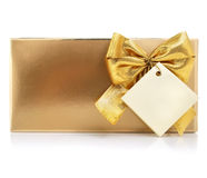 Gift with gold bow and blank label Royalty Free Stock Photos