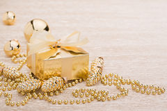 Gift and gold christmas ball on illuminated background. Gift and gold christmas balls on illuminated background Royalty Free Stock Images