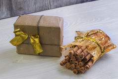 Gift with gold ribbon and a bag of wafer rolls Stock Image