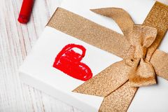 Gift with gold ribbon and red heart drawing. Copy space royalty free stock images