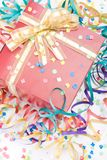 Gift with a golden bow. Red gift with a golden bow in a party setting Stock Photography