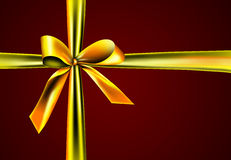 Gift with golden ribbon. A golden ribbon with a knot isolated on red Stock Photography