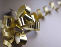 Gift golden ribbon. And bow on brown background Royalty Free Stock Photos