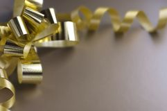 Gift golden ribbon. And bow on brown background Stock Image