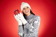 Gift guessing. Portrait of happy girl in winterwear holding giftbox by her ear Royalty Free Stock Photography