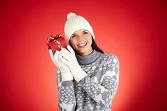 Gift guessing. Portrait of happy girl in winterwear holding giftbox by her ear Stock Images