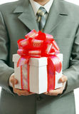 Gift in hands of the businessman. The businessman offering to you a gift Stock Photography