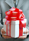 Gift in hands of the businessman. The businessman offering to you a gift Royalty Free Stock Photo