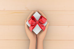 Gift. Hands holding gift box on wooden background 3d rendering Stock Photo