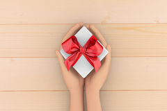 Gift. Hands holding gift box on wooden background 3d rendering Royalty Free Stock Photos