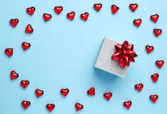 Gift and hearts on blue background Royalty Free Stock Photo