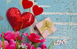 Gift and hearts on light blue  wooden board Royalty Free Stock Image