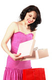 Gift for her. A very happy woman in pink dress opening paper box, isolated on white Royalty Free Stock Images