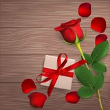 Gift for the holiday. Red rose, gift box and rose petals on wooden background. Greeting card for Valentine`s day, women`s day, mother`s day, birthday. Top view Royalty Free Stock Photos