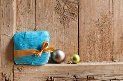 Free Gift In A Beautiful Package And Tied With A Ribbon And Two Christmas Balls On Old Wooden Background Wall. Royalty Free Stock Photo - 133835935
