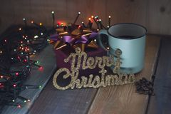 Gift, the inscription Marry Christmas and cup on the table Stock Photo