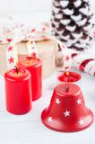 Gift in kraft box with red stars ribbon, lit candles and decorat Stock Image