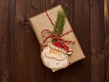 Christmas gift in kraft paper decorated with spruce branches and wooden Santa Claus Royalty Free Stock Photo